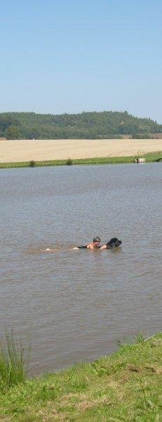 Za obojek psa se drží zachráněná osoba.